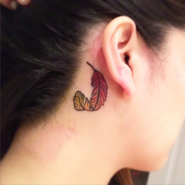 small phoenix feather tattoo behind the ear