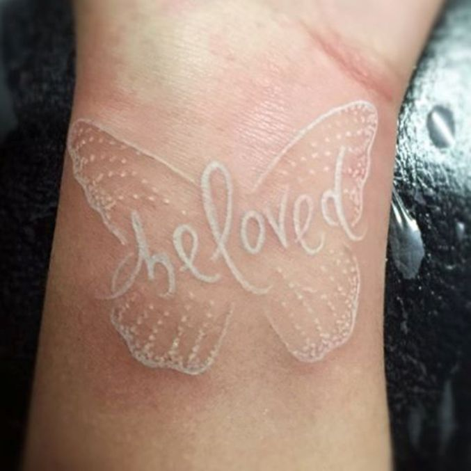 white ink butterfly tattoo on wrist
